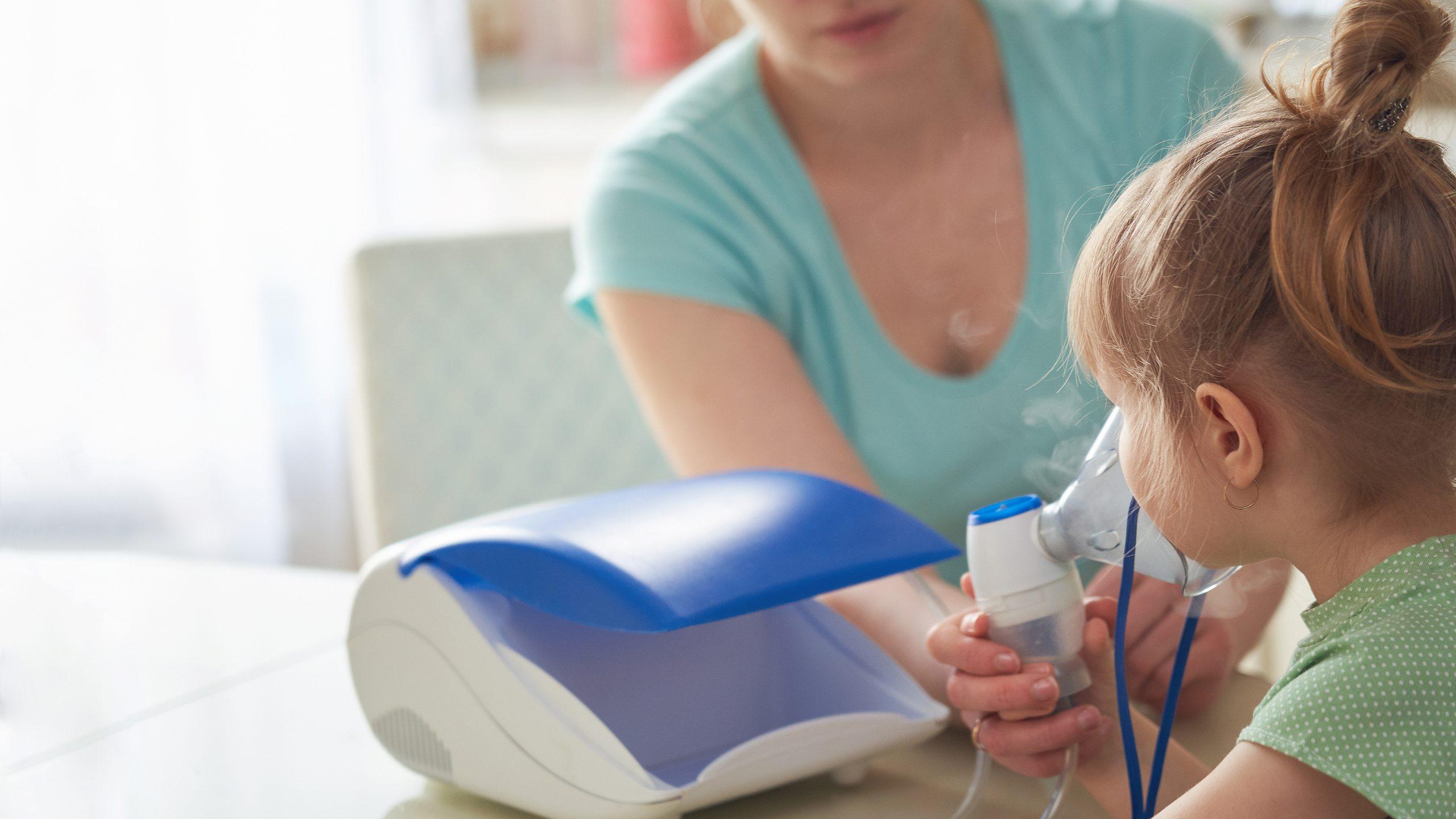 Matka dává inhalátor dítěti s černým kašlem