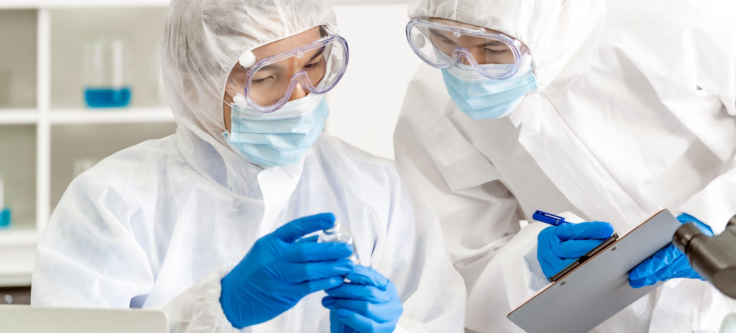 Dva lékaři v rouškách a ochranných oblecích zkoumající očkovací látku