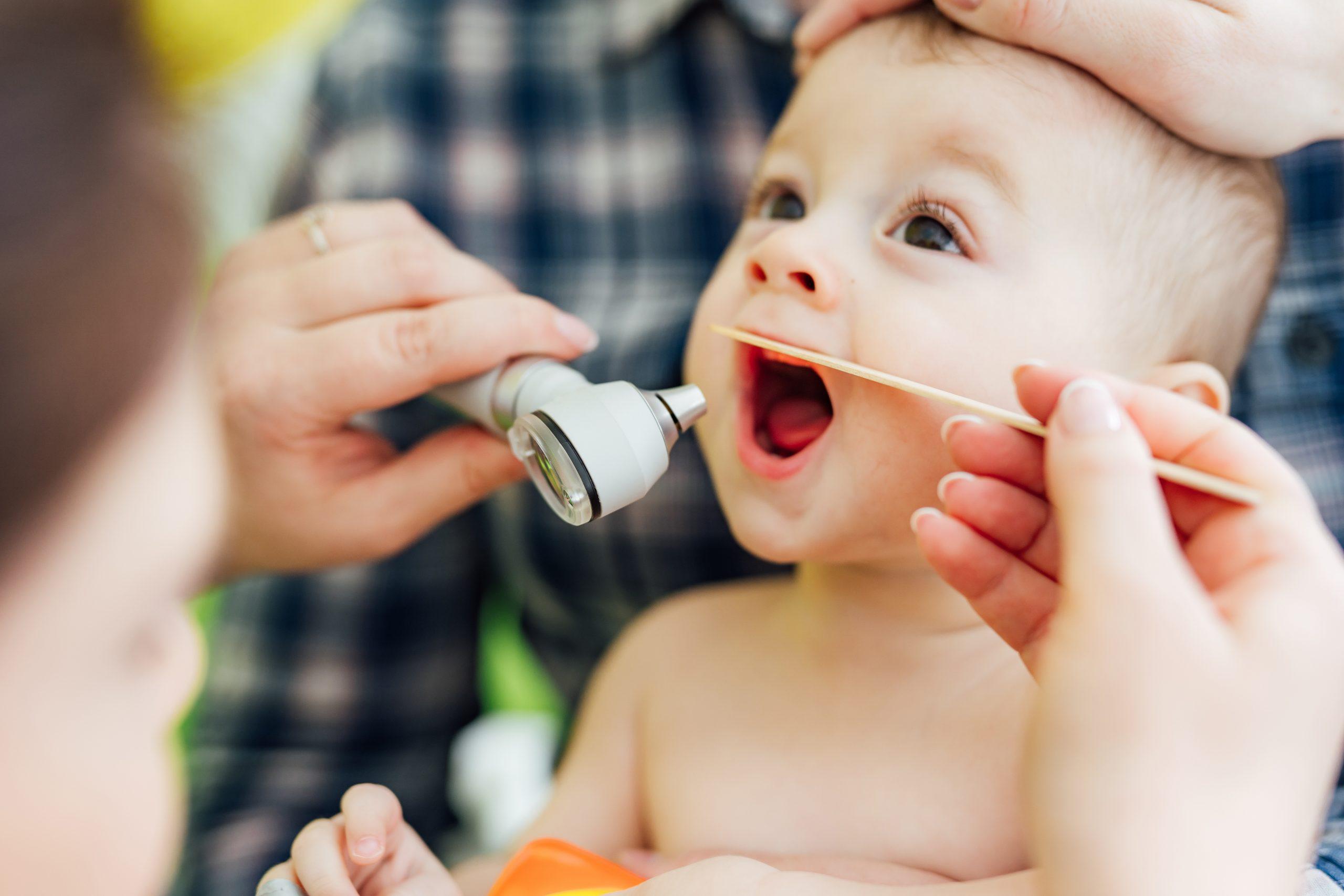 Pediatrička vyšetřuje dítě a kontroluje mu hrdlo.