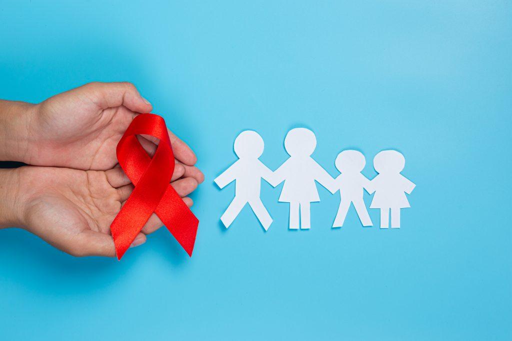 Ženská ruka drží červenou stužku - symbol HIV. Vedle je z papíru vystřižený symbol rodiny.