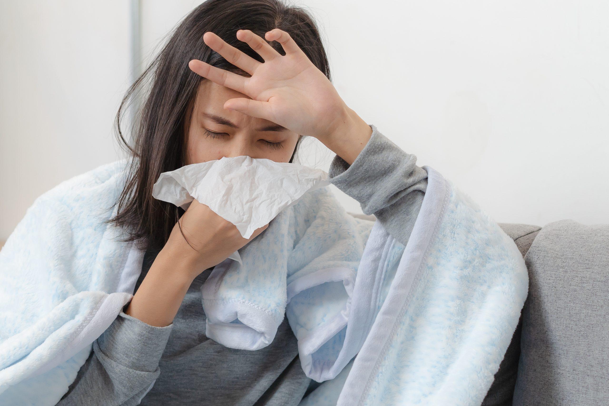 Žena sedí na pohovce, má chřipku.