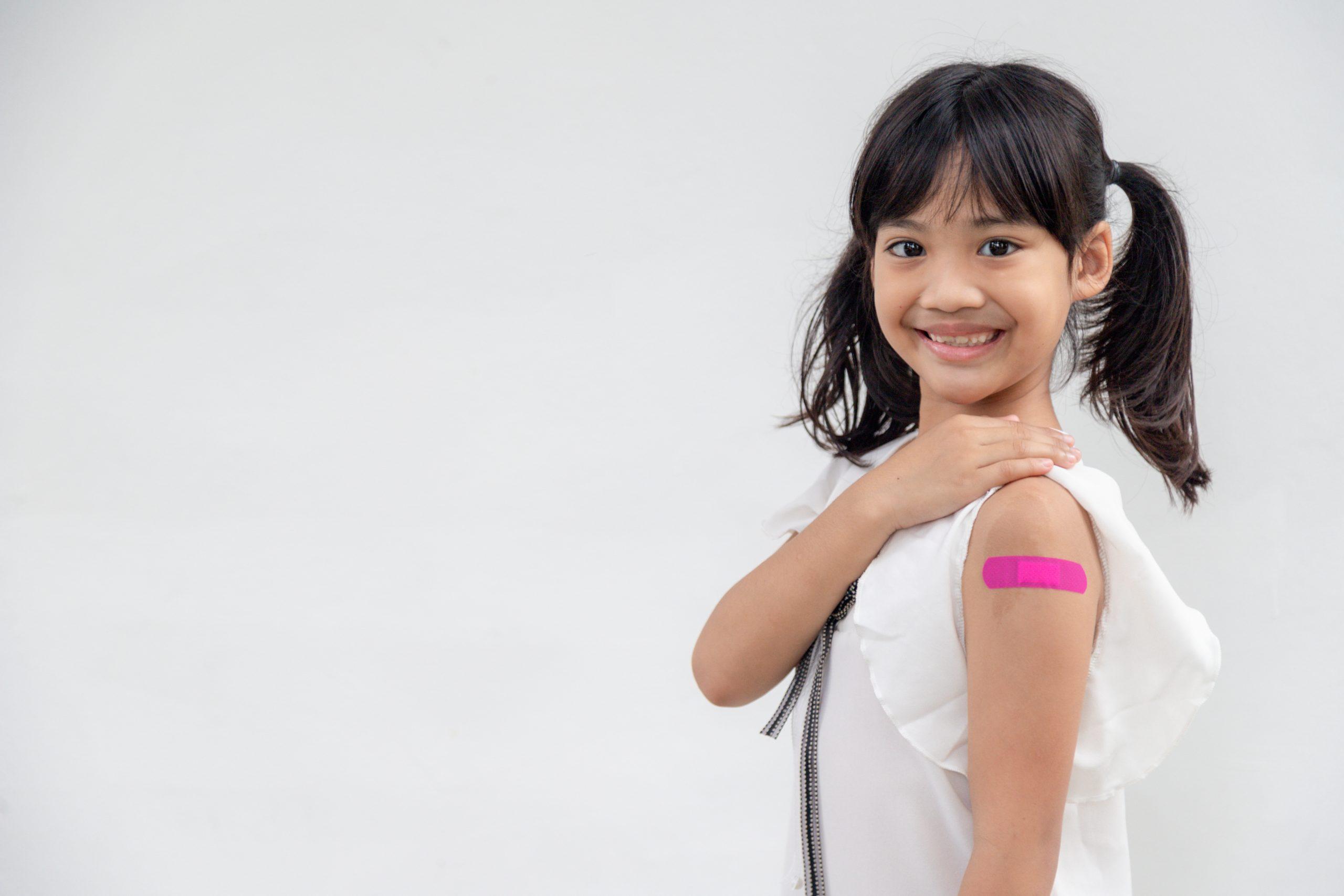 Holčička ukazující ruku po očkování.