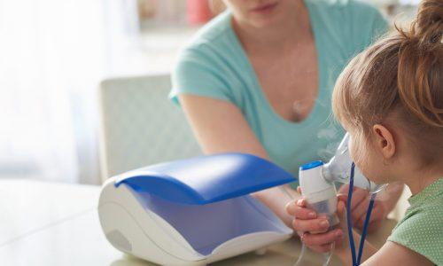 Matka dává inhalátor dítěti s černým kašlem.