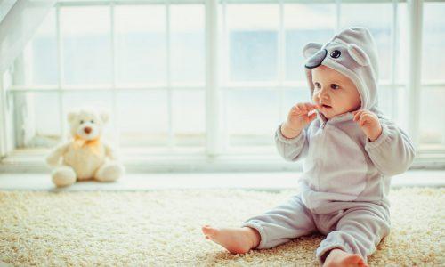 Malý chlapec sedí při okně.