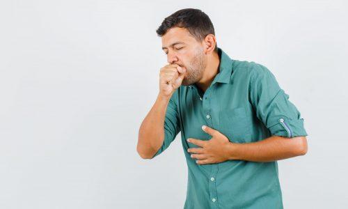 Kašlající mladý muž v košili.